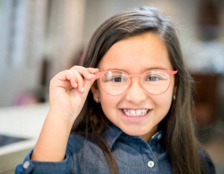 young girl holding glasses and smiling