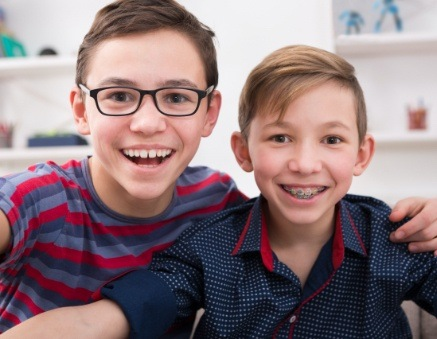 two brothers one with glasses one with braces smiling