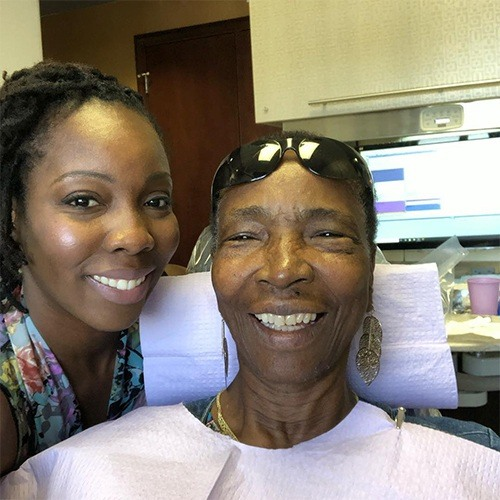 Dr. Delica smiling with patient in chair